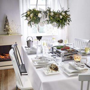 Raclettegrill auf gedecktem Tisch mit Raclette Zubehör